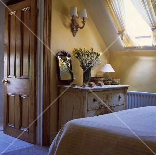 Weissliche antike holzkommode unter dachfl chenfenster in gelb weissem schlafzimmer mit offener - Antike badezimmer ...