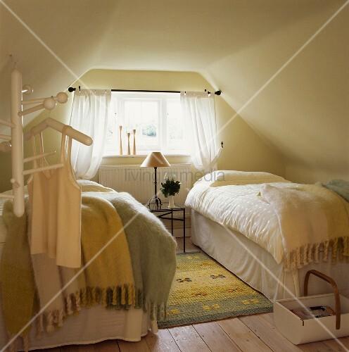 pastellfarbene mohairdecken auf zwei einzelbetten in schlafzimmer unterm dach mit dielenboden. Black Bedroom Furniture Sets. Home Design Ideas