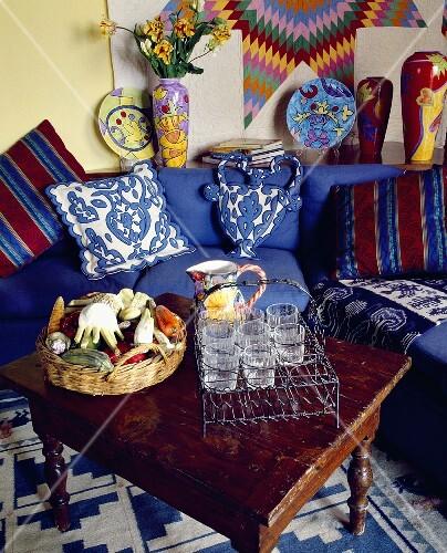 ein rustikaler holztisch mit gl sern vor der blauen sofa mit bunten kissen bild kaufen. Black Bedroom Furniture Sets. Home Design Ideas