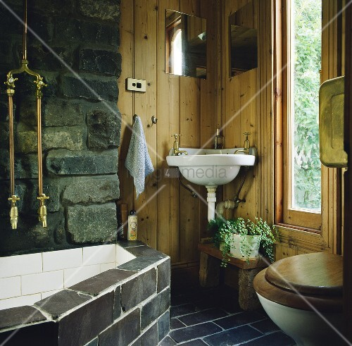 ein schwarzer fliesenboden umgibt ein rustikales badezimmer mit einem eck waschbecken das auf. Black Bedroom Furniture Sets. Home Design Ideas