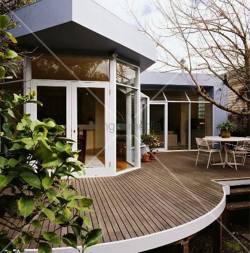 ein architektonisches haus mit einer gebogenen dachterrasse die zum privaten gartenbereich. Black Bedroom Furniture Sets. Home Design Ideas