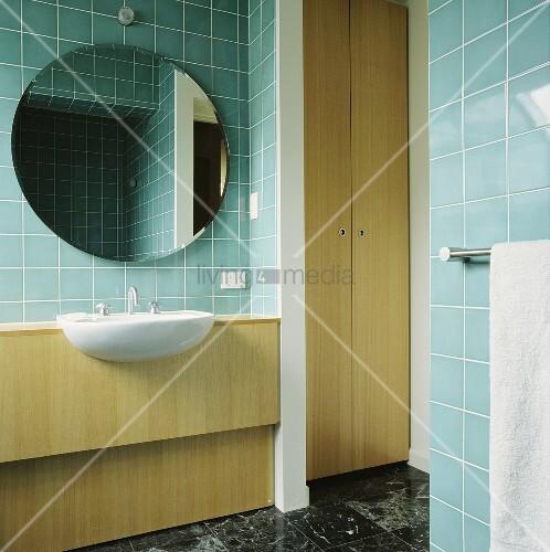 in einem t rkis gefliesten bad h ngt ein kreisf rmiger spiegel ber einem waschbecken das in. Black Bedroom Furniture Sets. Home Design Ideas