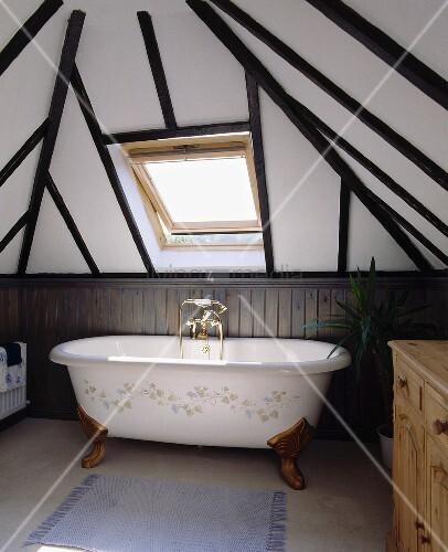Eine freistehende Badewanne steht unter einem Velux ...