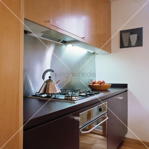 eine kleine moderne k che mit holz einheiten und einer edelstahl r ckwand bild kaufen. Black Bedroom Furniture Sets. Home Design Ideas