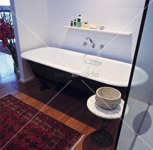 eine schwarze freistehende badewanne und ein orientalischer teppich auf dem parkettboden statten. Black Bedroom Furniture Sets. Home Design Ideas