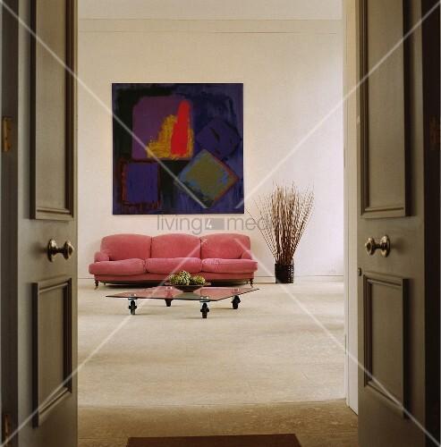 ein couchtisch aus glas und ein pinkfarbenes sofa unter einem abstrakten bild bild kaufen. Black Bedroom Furniture Sets. Home Design Ideas