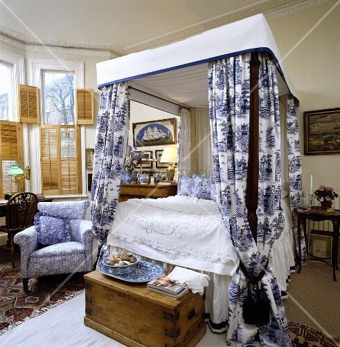 Schlafzimmer mit Himmelbett, blau-weiss gemusterten Bett-Vorhängen ...
