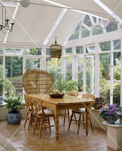 wintergarten mit weissen jalousien einem holztisch und holzst hlen bild kaufen living4media. Black Bedroom Furniture Sets. Home Design Ideas