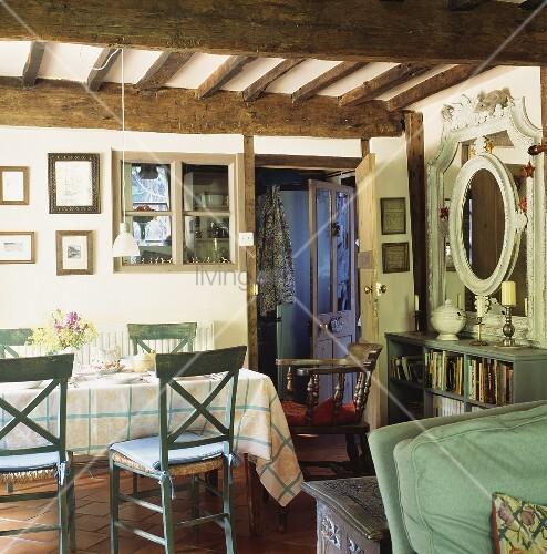 blaugr ne st hle und karierte tischdecke auf esstisch unter rustikaler holzdecke im landhaus. Black Bedroom Furniture Sets. Home Design Ideas