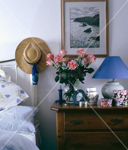 rosen in vase auf antik rustikalem nachttisch und strohhut auf messinggestell am kopfende vom. Black Bedroom Furniture Sets. Home Design Ideas