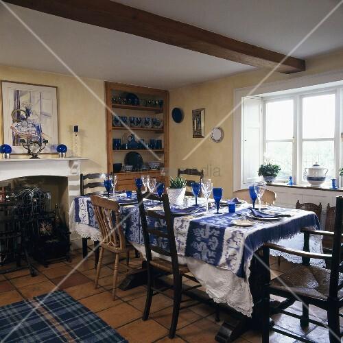 gedeckter esstisch mit blauen stielgl sern und verschiedenen st hlen im schlichten esszimmer. Black Bedroom Furniture Sets. Home Design Ideas