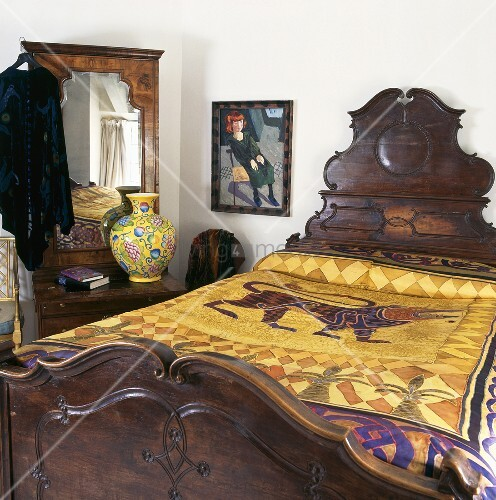 antikes bett mit kopfteil aus dunklem holz und goldfarbener tagesdecke mit orientalischem motiv. Black Bedroom Furniture Sets. Home Design Ideas