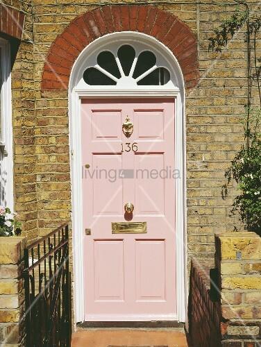rosa lackierte haust r mit oberlicht im traditionellen haus mit ziegelfassade bild kaufen. Black Bedroom Furniture Sets. Home Design Ideas