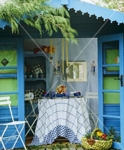 blau gestrichenes gartenhaus mit offenen t ren und und. Black Bedroom Furniture Sets. Home Design Ideas