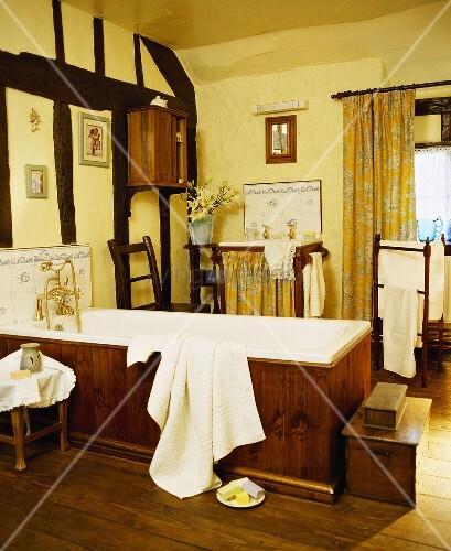 gelb get ntes badezimmer mit holzverkleideter badewanne und wand mit fachwerkkonstruktion bild. Black Bedroom Furniture Sets. Home Design Ideas