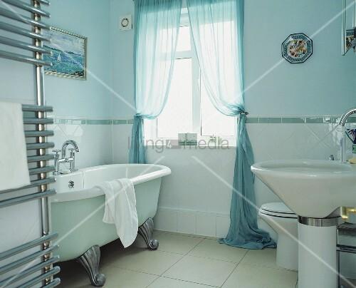 modernes badezimmer mit freistehender badewanne im vintagelook vor hellblauer wand bild kaufen. Black Bedroom Furniture Sets. Home Design Ideas