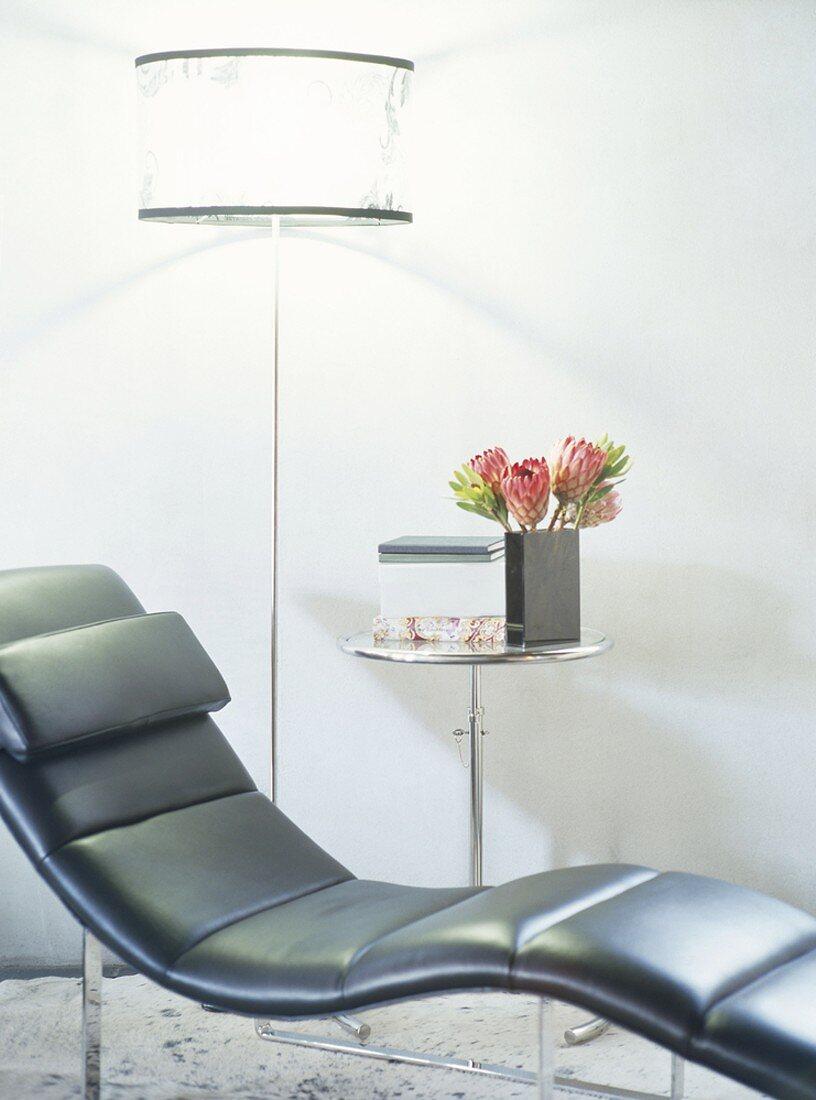 Geschwungener Liegestuhl aus schwarzem Leder neben Stehlampe