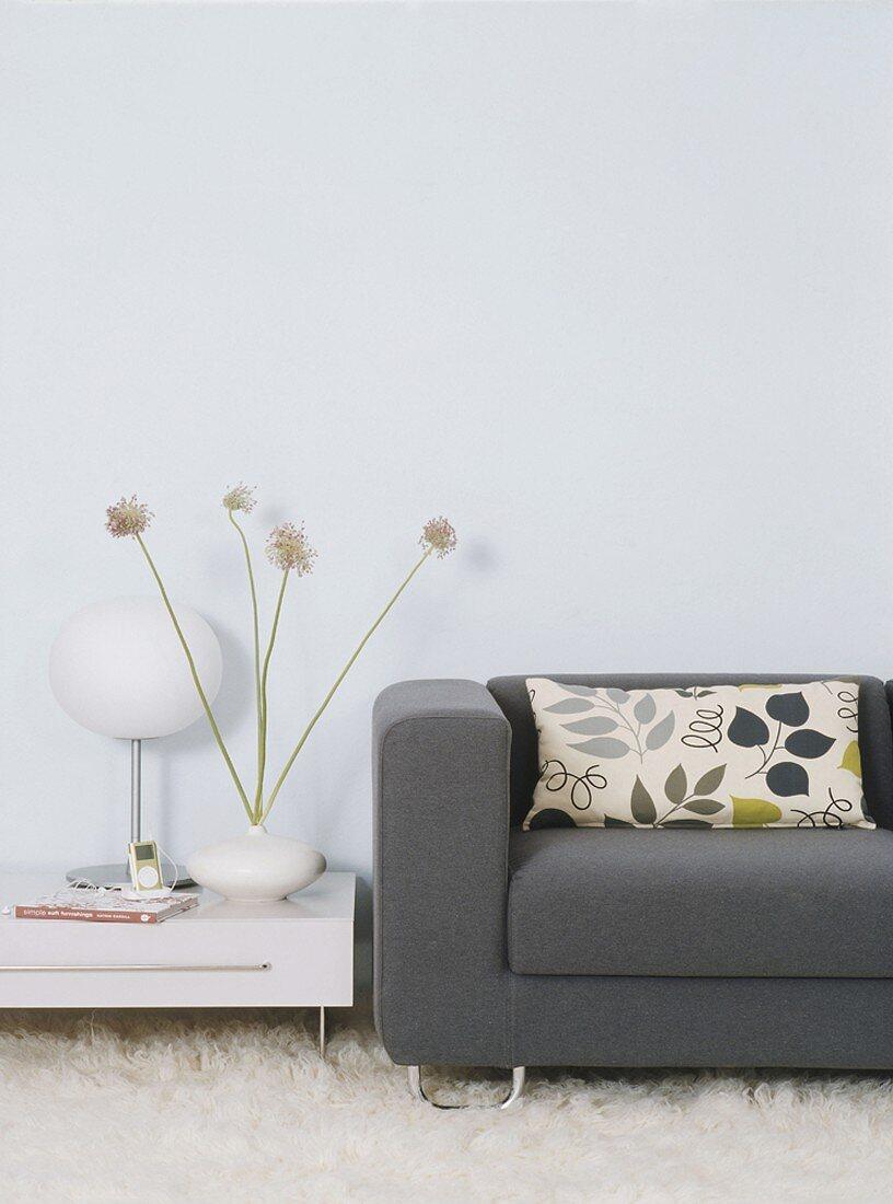 Ein graues Stoffsofa und ein niedriger weißer Abstelltisch auf Schaffell