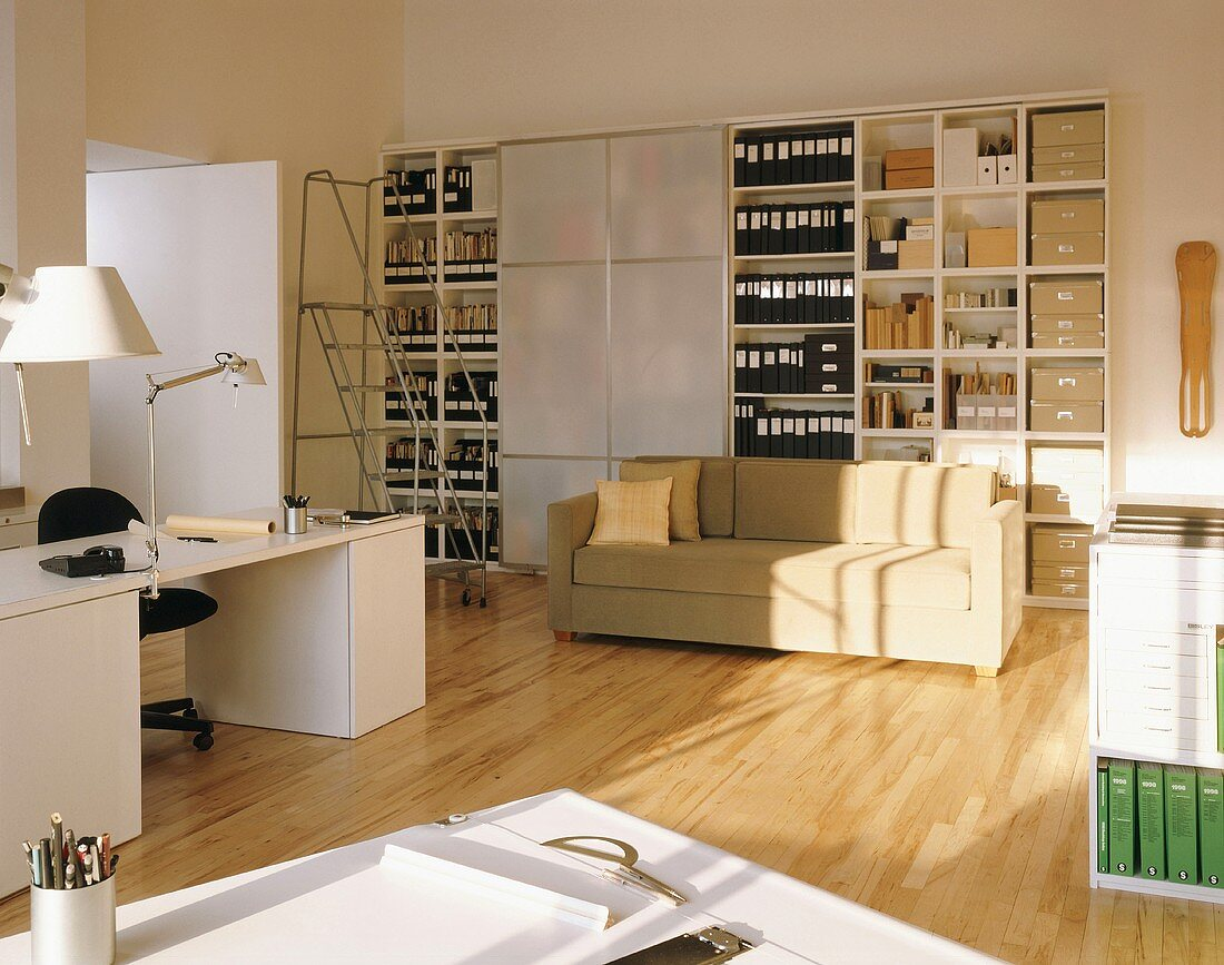 Large office cupboard with sliding doors in spacious office with desk, drawing table and couch
