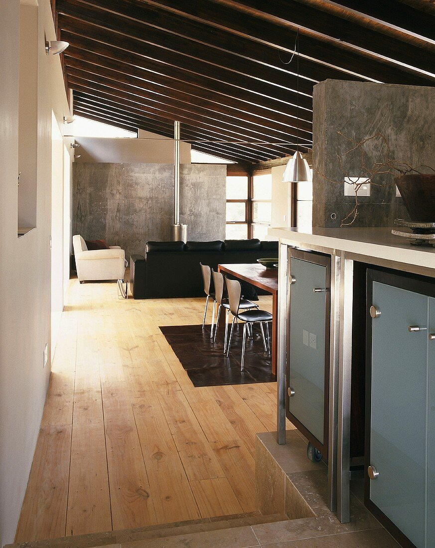 View from kitchen into open-plan, modern interior with sloping roof beams, concrete wall and pale wooden floor