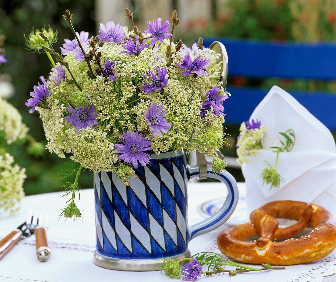 Chicory flowers & cow parsley in Bavarian beer mug, pretzel