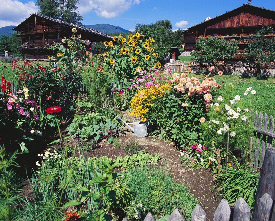 Kleiner Garten mit Blumen, Kräutern & Gemüse vor zwei Holz-Bauernhütte