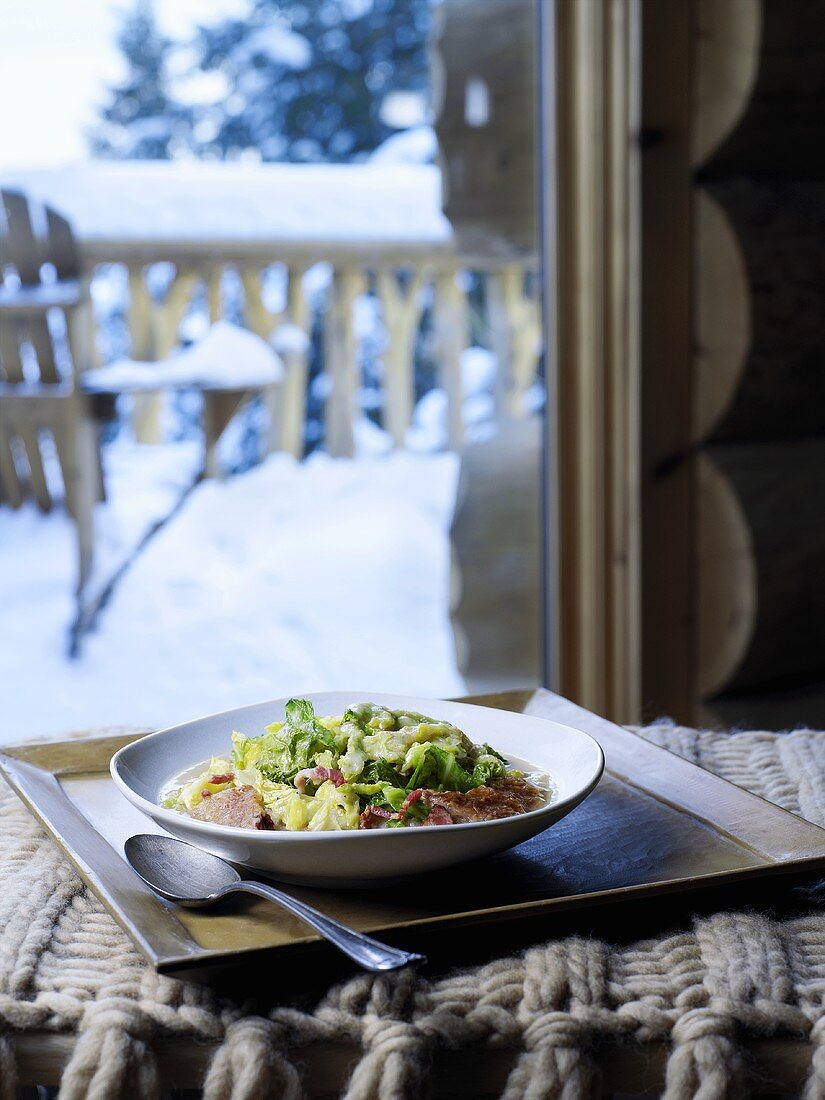 Cabbage and bacon dish, snow-covered garden in background