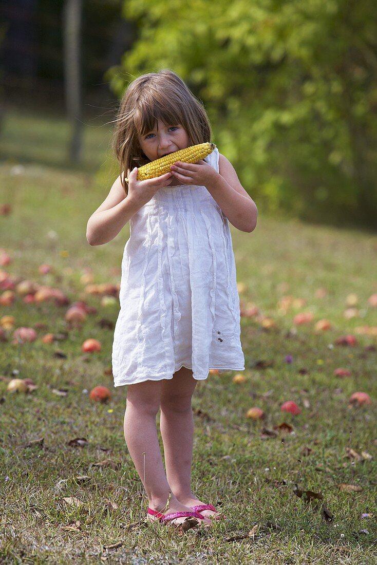 A girl eating a corn cob in a garden