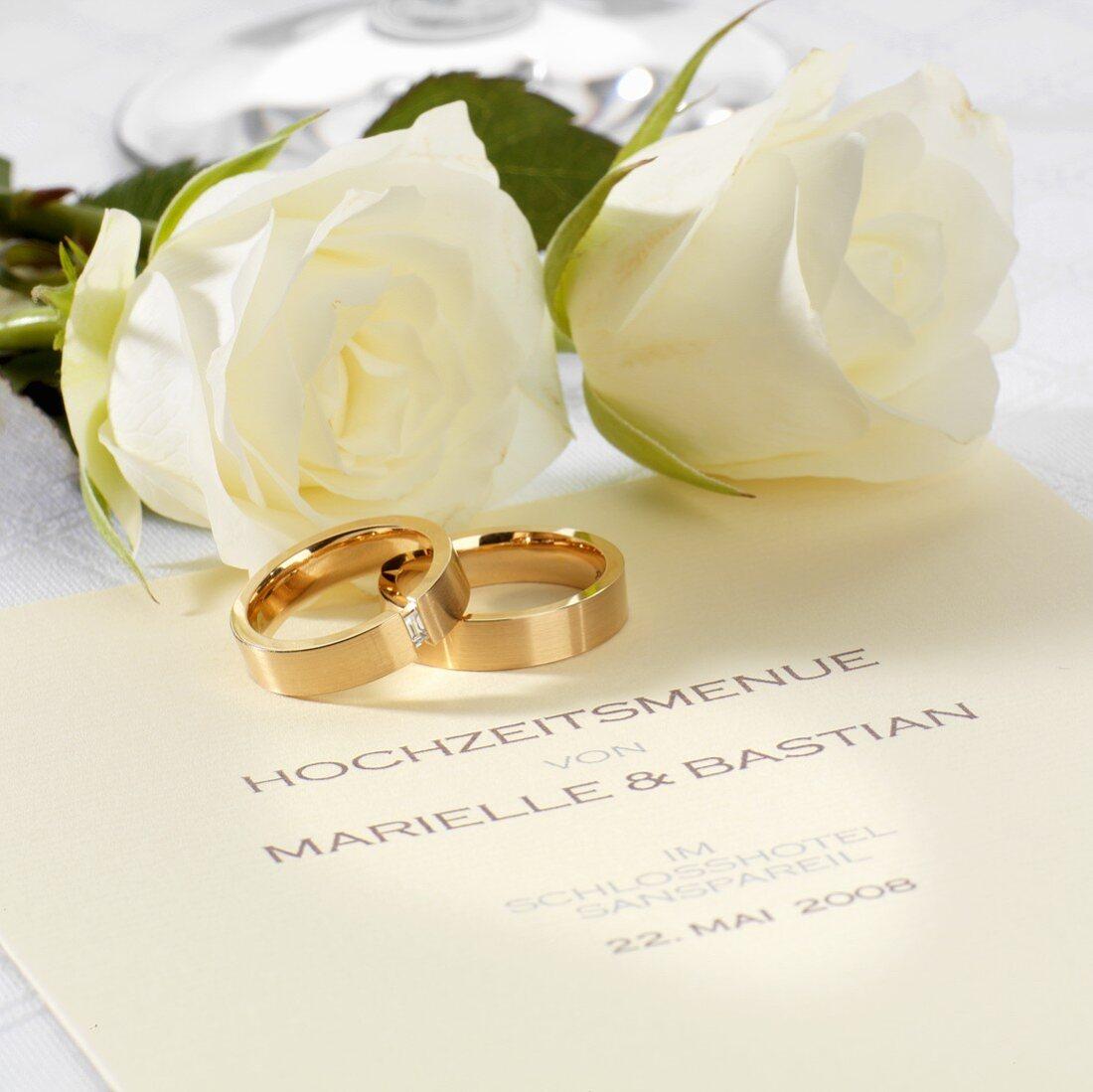Wedding menu, wedding rings and white roses