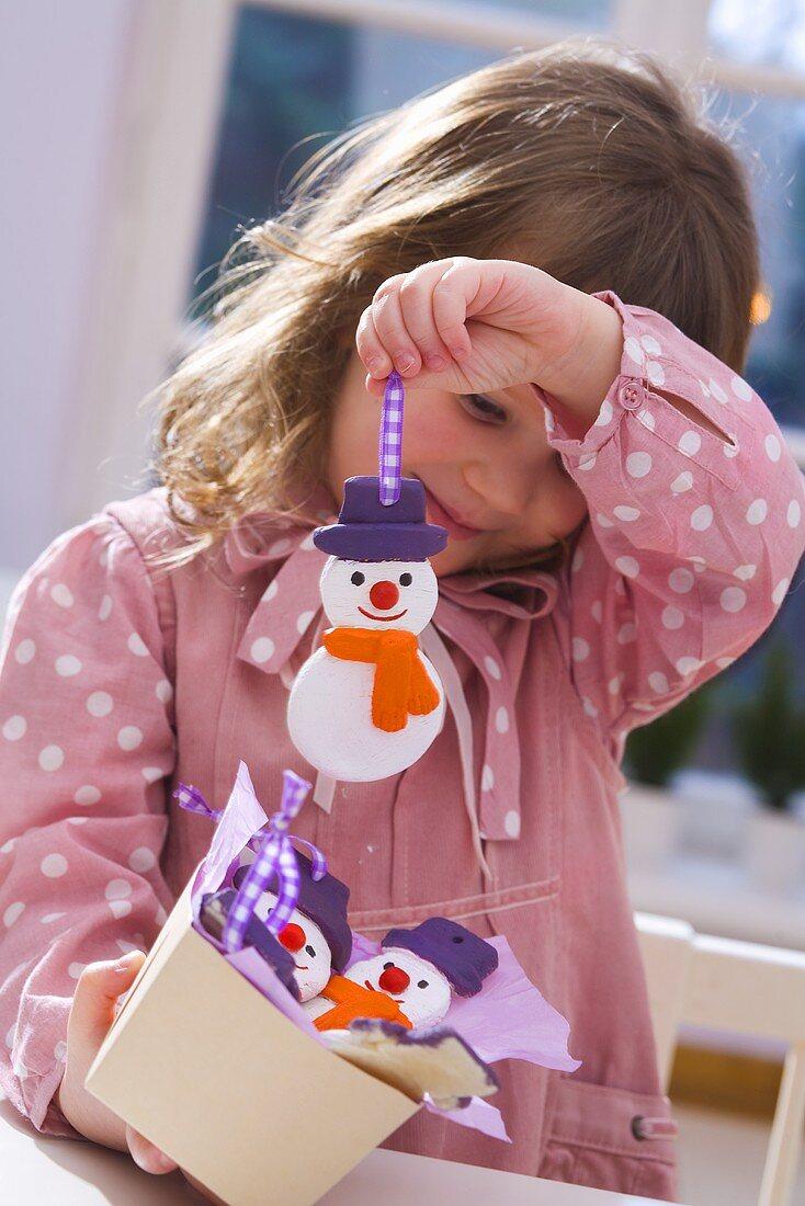 Girl holding salt dough snowman (tree ornament)