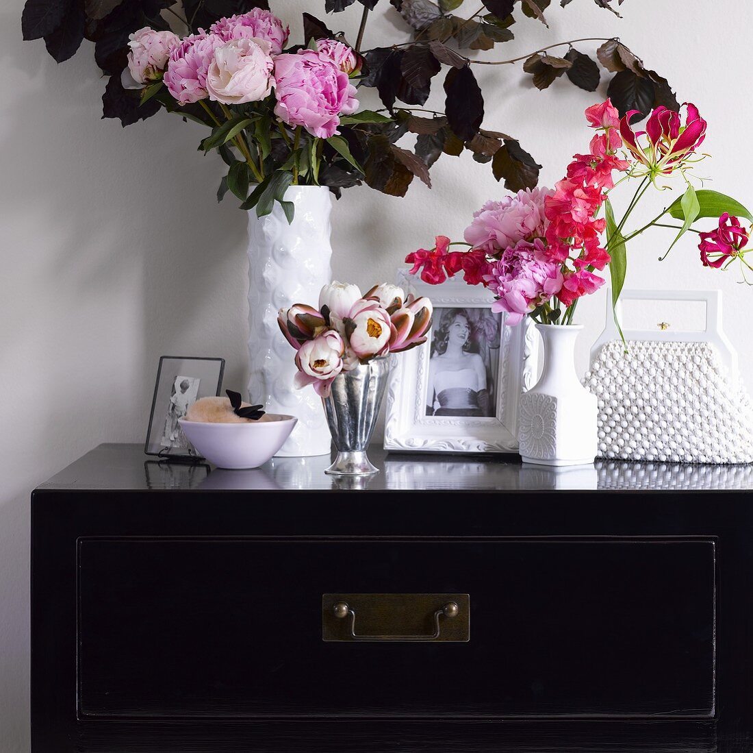 Vases of flowers, photos and handbag on black chest of drawers