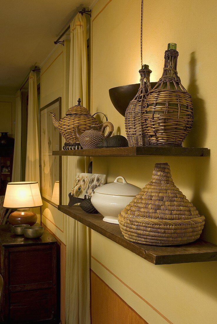 Wicker bottles on wooden shelves