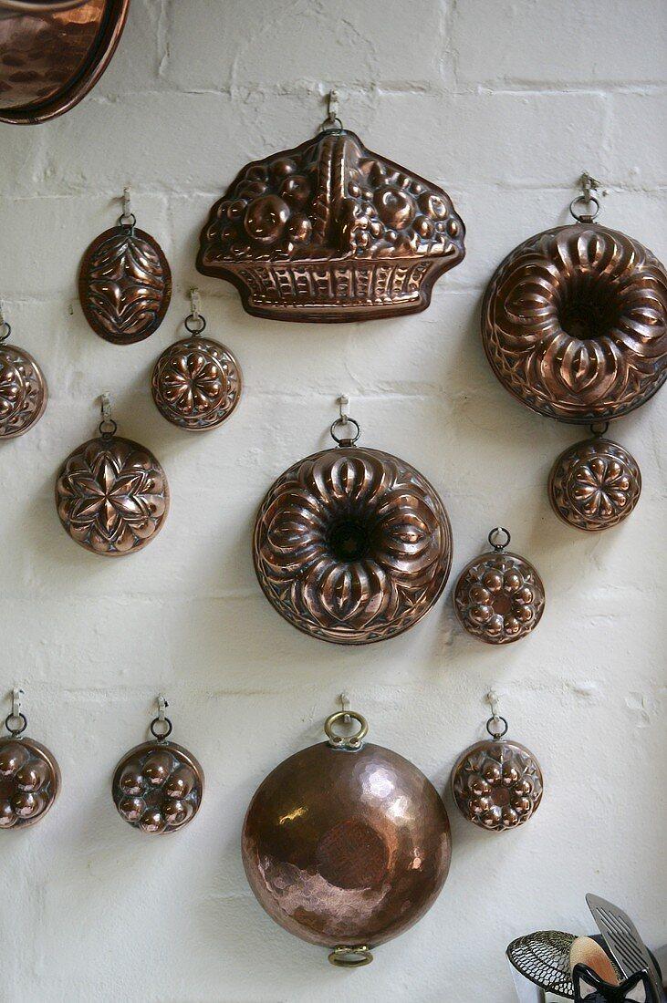 Various Bundt cake tins hanging on a kitchen wall