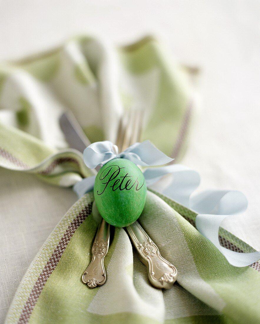 serviette und besteck mit grünem osterei  bild kaufen