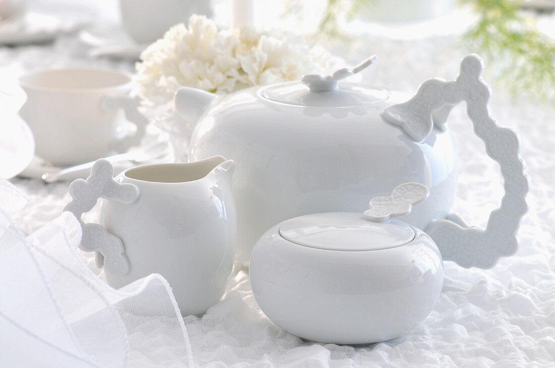 A white tea pot with a sugar bowl and a milk jug on a white table cloth
