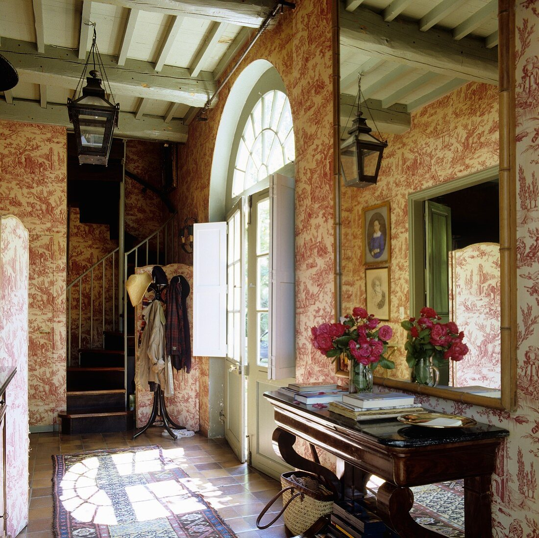 A hallway with patterned wallpaper on the wall and a large mirror over a wall table in a French country house