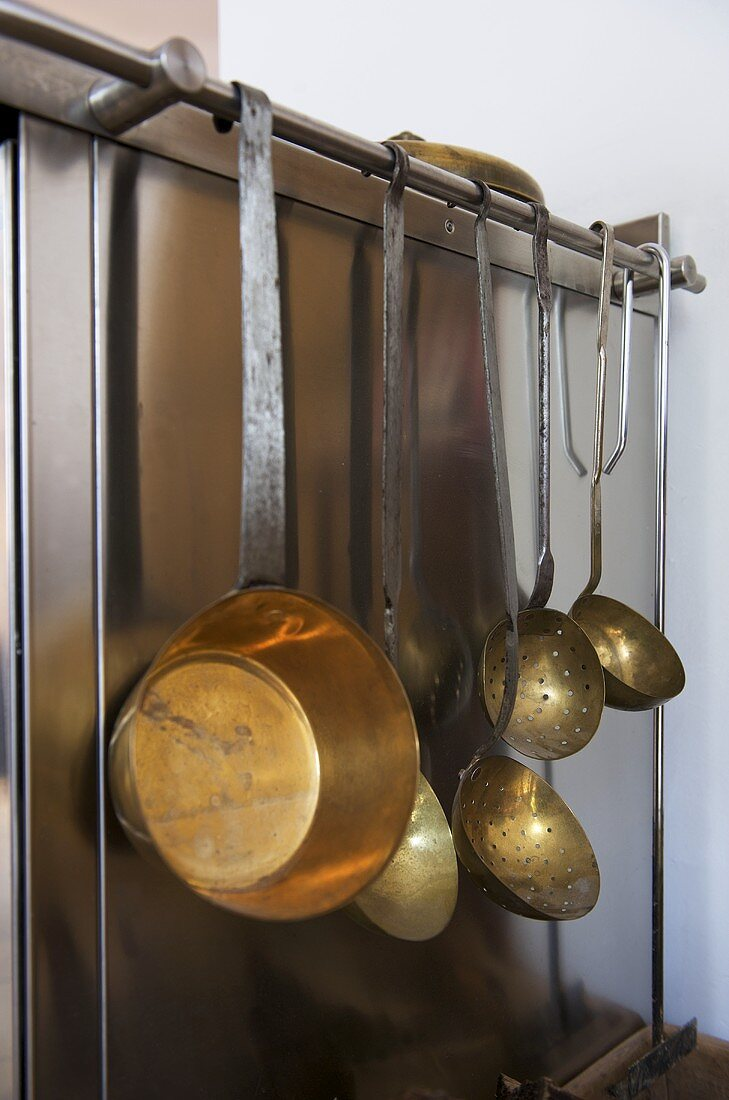 Copper cookware hanging beside oven