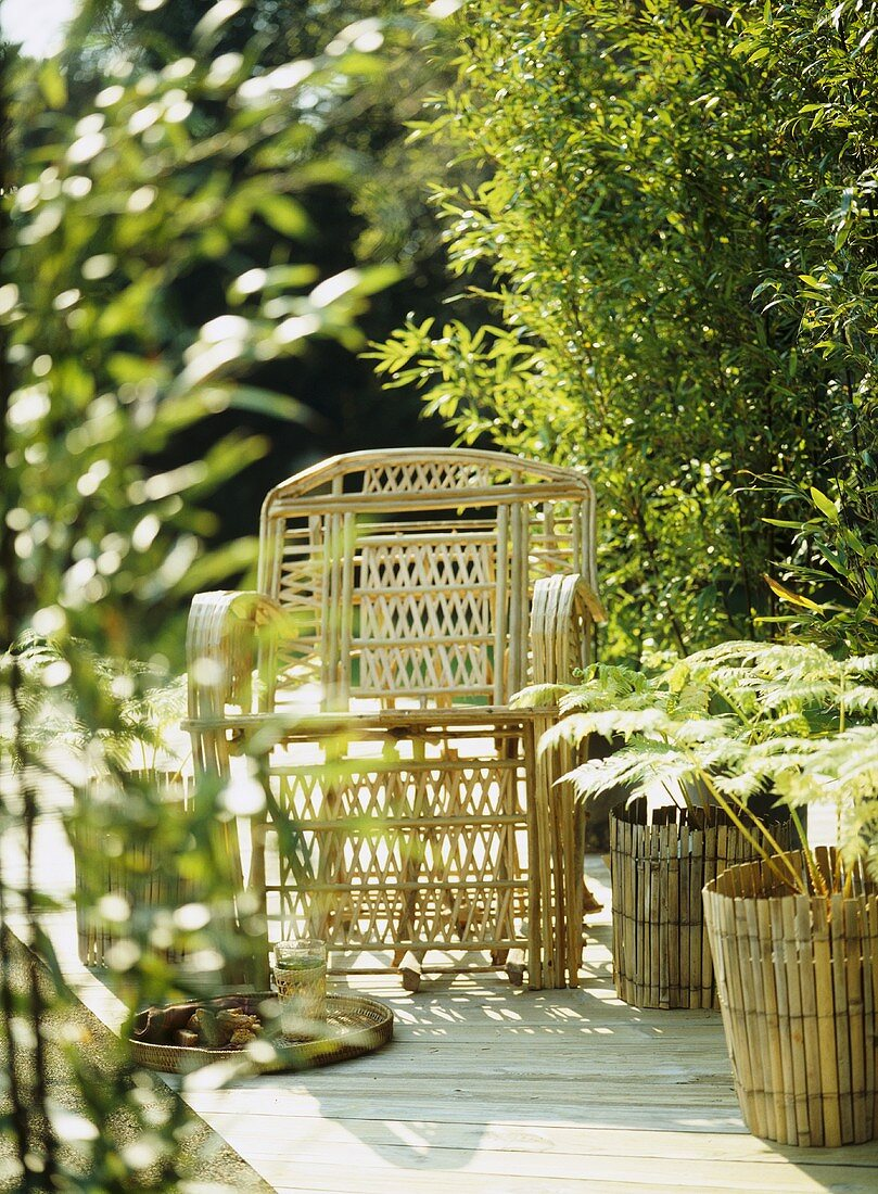 A detail of a decked garden patio, showing a bamboo cane chair and plant containers