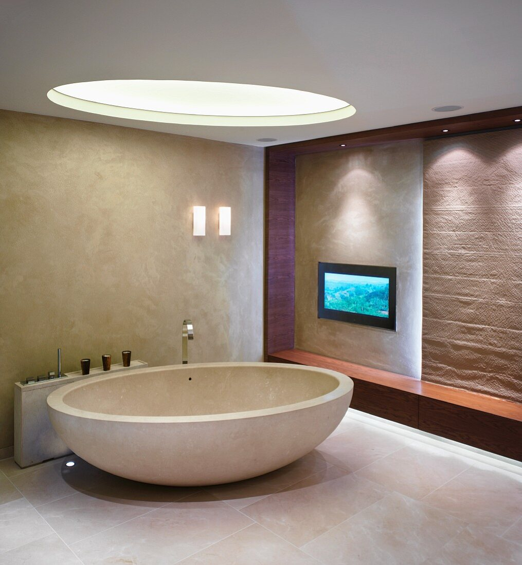 Oval, free standing bathtub with designer fittings under a round skylight