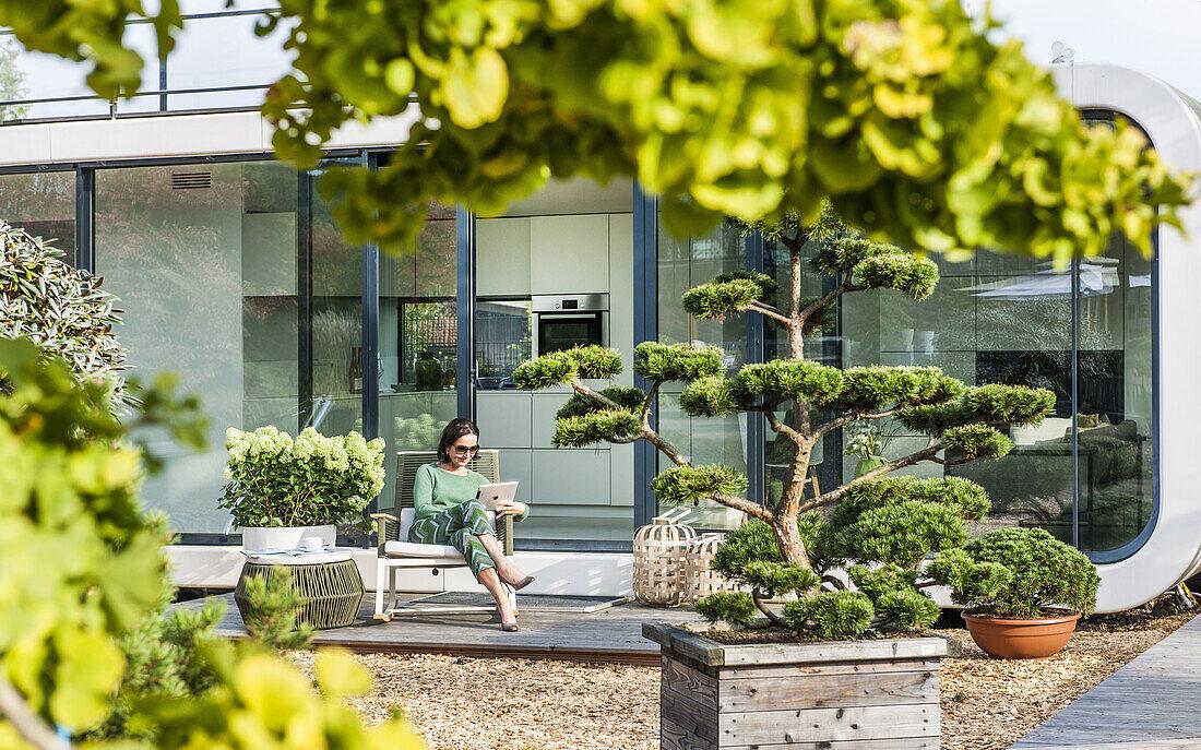 Frau sitzt auf einer Terasse und liest im iPad, coodo moderne Art zu Wohnen, moderne Architektur in Hamburg, Hamburg, Norddeutschland, Deutschland