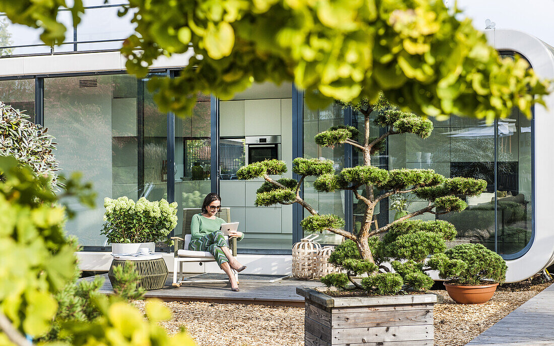 woman sitting on a terrace with an iPad, coodo modern way of living, modern architecture in Hamburg, north Germany, Germany