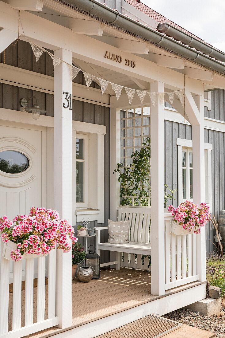 Veranda von selbstgebauten Eigenheim mit weißer Bank und Blumenkörben im Sonnenlicht, Korbach, Hessen, Deutschland, Europa