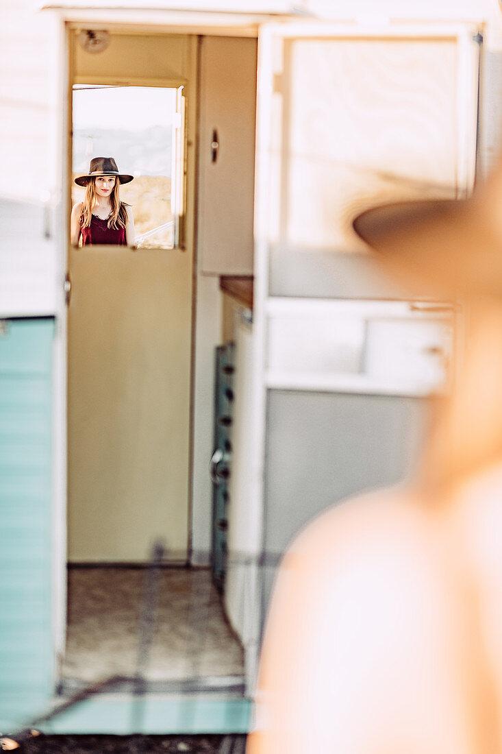 Frau mit Spiegelbild vor Caravan im Joshua Tree National Park, Joshua Tree, Los Angeles, Kalifornien, USA, Nordamerika