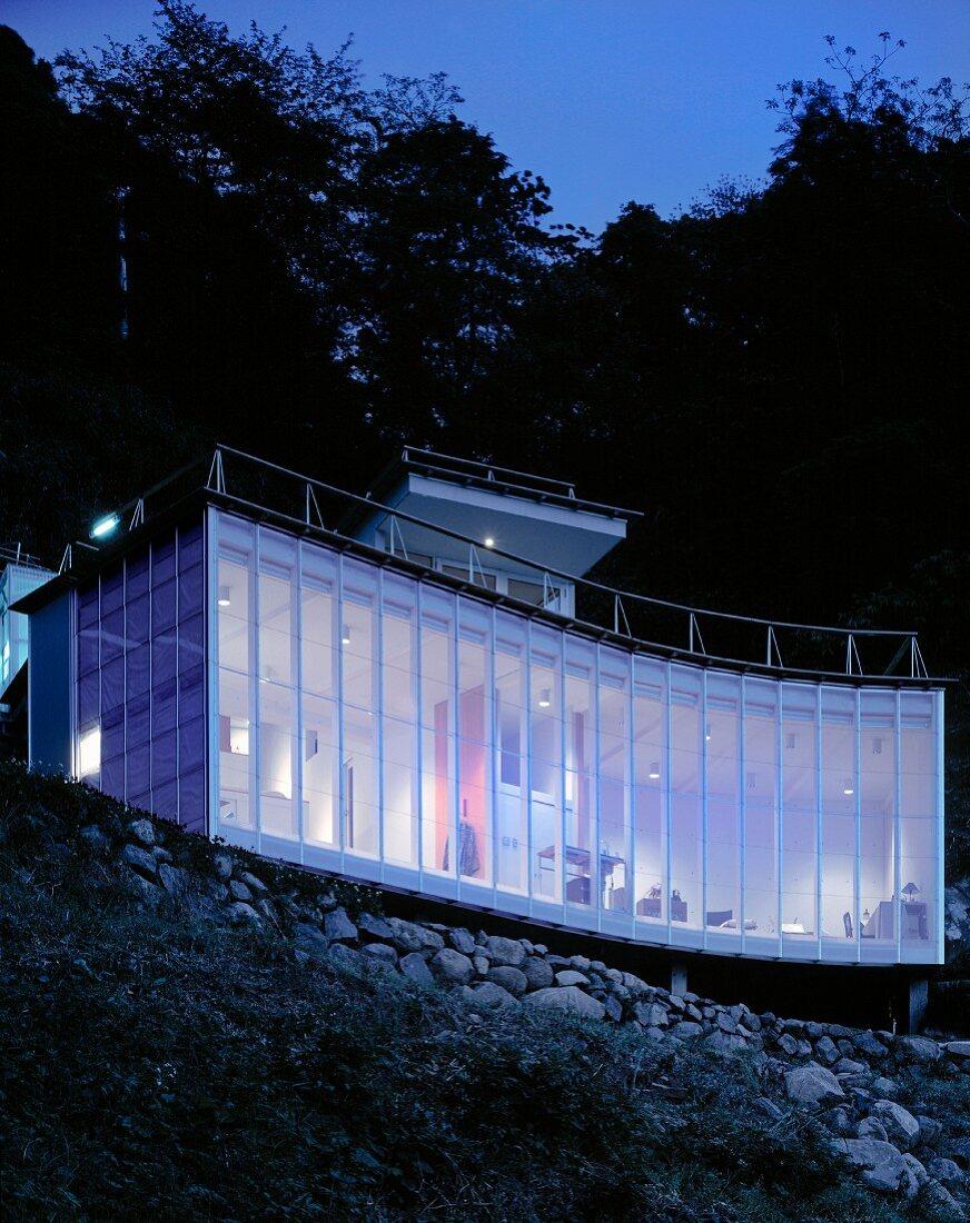 Neubauhaus mit geschwungener Fassade am Hang in Abendstimmung, Haus Izu von Atelier Bow-Wow, Tokio, Japan