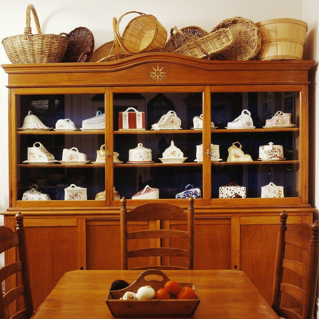 Körbesammlung auf schlichter, alter Holzvitrine mit Sammlung antiker Käseglocken hinter Essplatz in gleicher Holzfarbe
