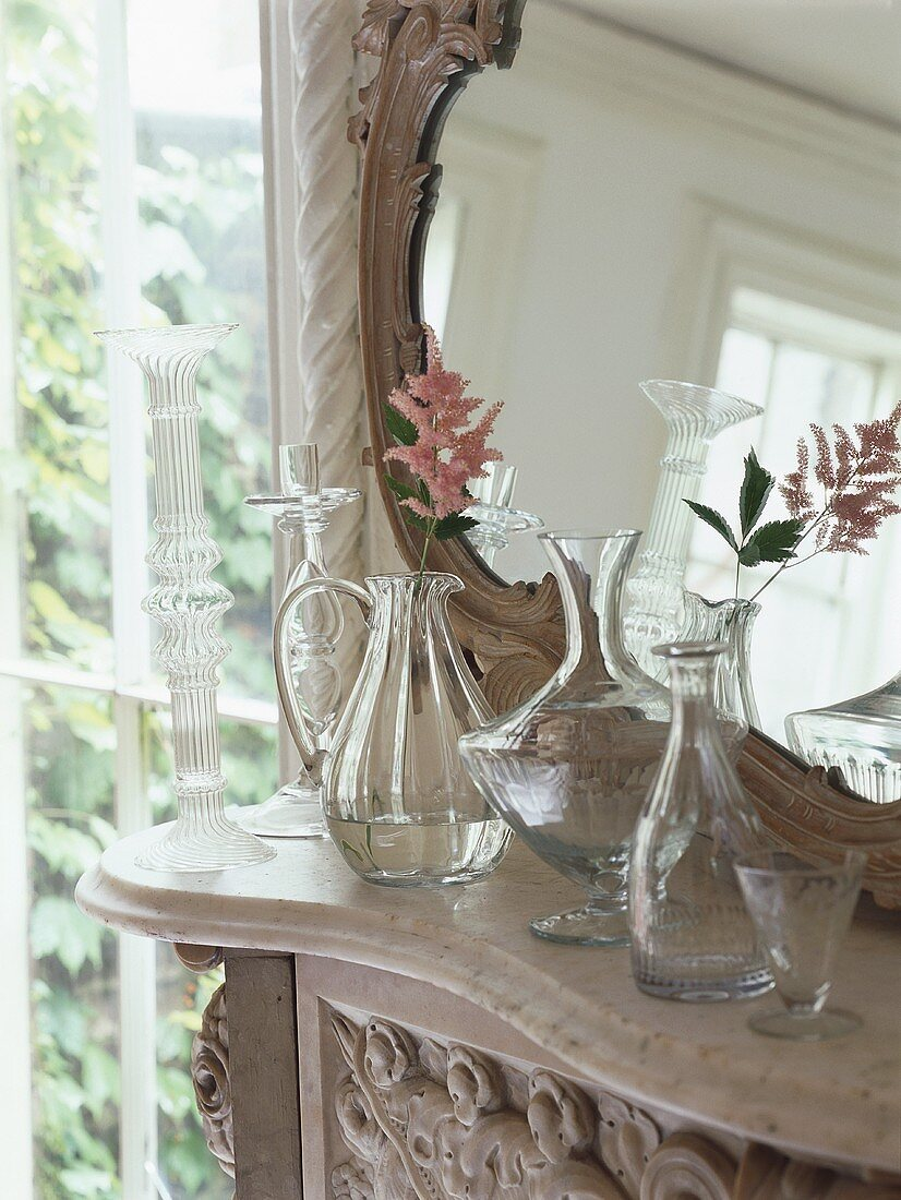 Delicate flowers in glass vases in front of mirror