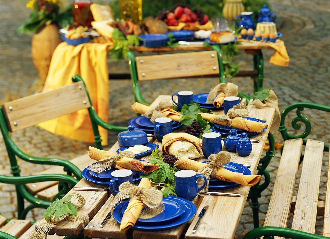 Wooden table laid with blue crockery in open air