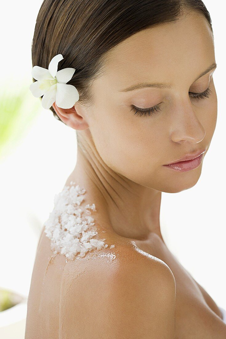 Portrait of young woman with a flower in her hair and exfoliating scrub on her back