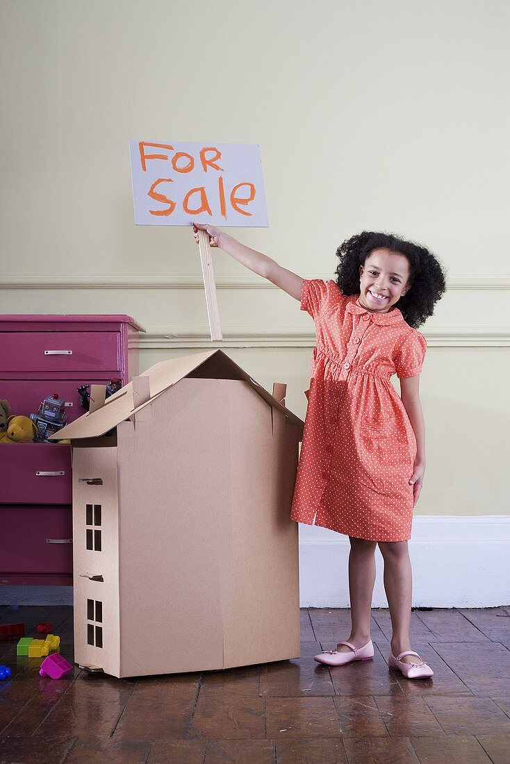 A girl with cardboard house and a For Sale sign