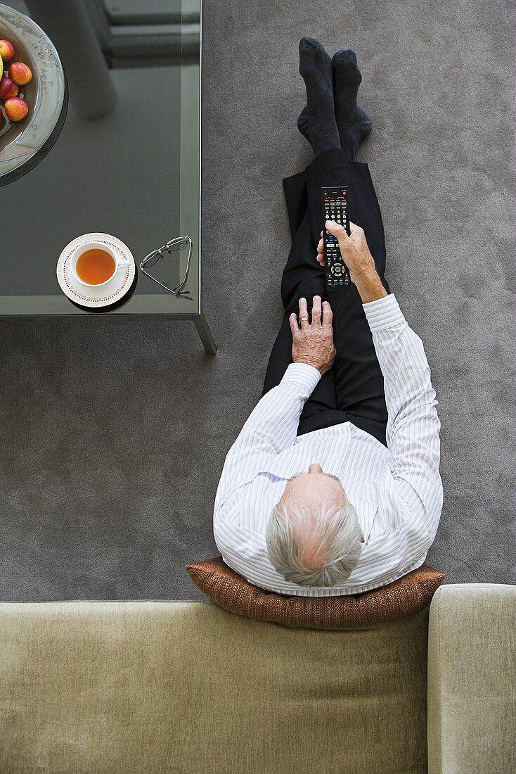 An older man watching television